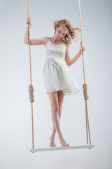 Young bare-footed girl on swing looking down.