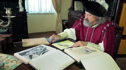 Old expert during writing his new ideas dressed in medival clothes