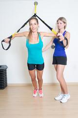 Weiblicher Trainer hilft beim Schlingentraining