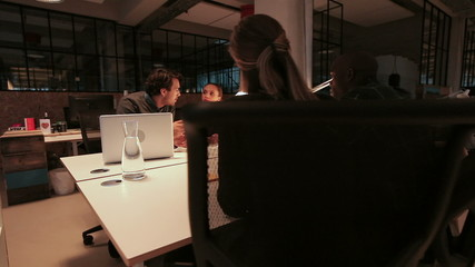 Four young people sitting around a table making new business
