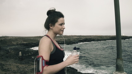 Woman drinking water while standing on rocks by sea