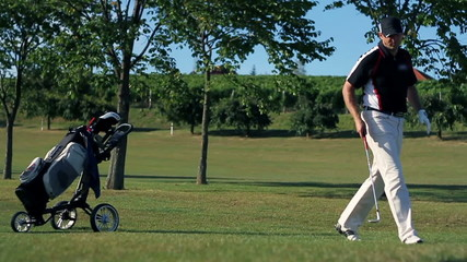 couple coming to golf course carring all the golf equipment