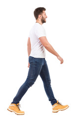 Young man walking in jeans and white t-shirt
