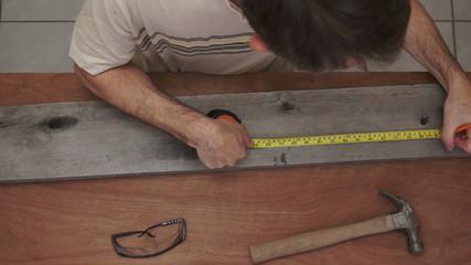 Industrial Carpenter Measuring Wood
