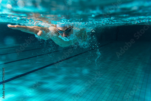 Poster, Tablou Male swimmer at the swimming pool.Underwater photo.