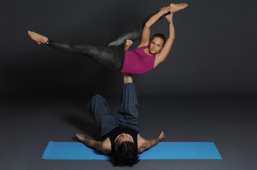 Woman and man doing acro yoga.