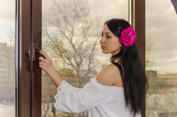Girl with long hair in a linen shirt in the window