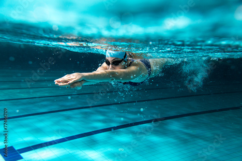 Poster, Tablou Female swimmer at the swimming pool.Underwater photo.