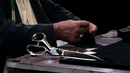 Close up shot of a tailor sewing  a button