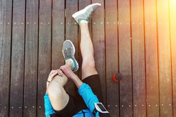 sportsman's legs sitting on the wooden floor