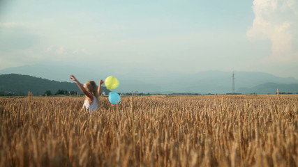 Little girl with colorful baloon running on a field