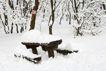 Snowy benches and red bike sign