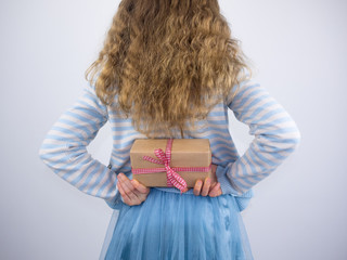 girl holding present behind back