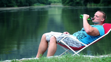 Young man relaxing in nature and drinking refreshing drink