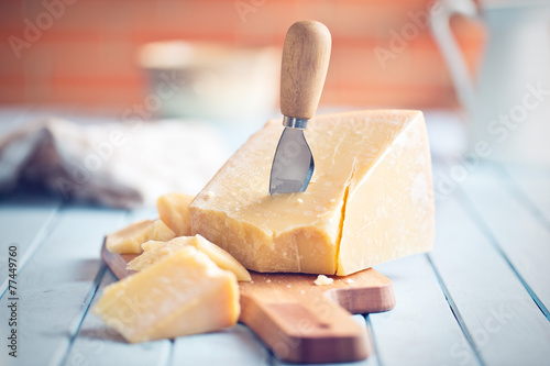parmesan cheese on cutting board - 77449760