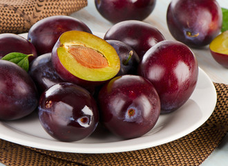 Fresh plums on a white plate