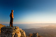 man on the cliff in mountains at sunset - 77450371