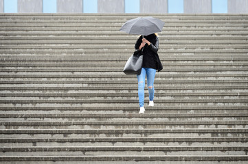 Young adult woman walks down the stairs in the rain