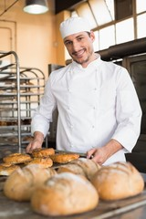 Happy baker taking out fresh bagels