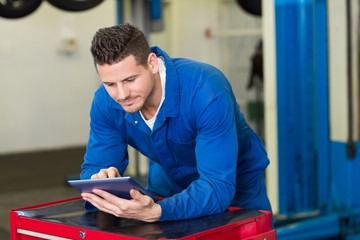 Smiling mechanic using his tablet