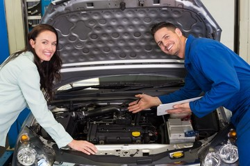 Mechanic smiling at the camera with customer