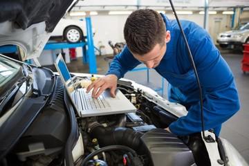 Mechanic using laptop on car