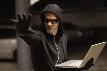 Hacker in balaclava gesturing and using laptop