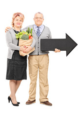 Mature couple holding groceries and an arrow