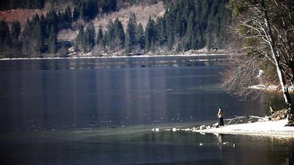 of a boy throwing stones on frozen Bohinj's lake