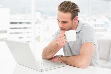 Focused businessman holding cup while using laptop