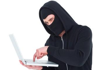 Hacker in balaclava typing on laptop