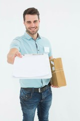 Delivery man with package giving clipboard for signature