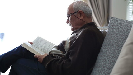 Senior Man Reading Book at Home