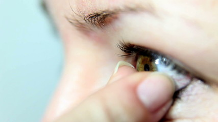 Close up shot of a woman putting a lense in her eye
