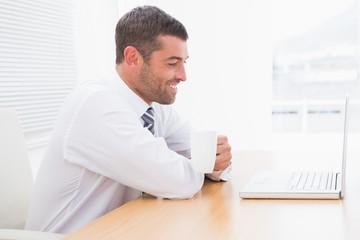 A businessman holding mug at desk