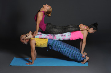 Two woman and man doing acro yoga.