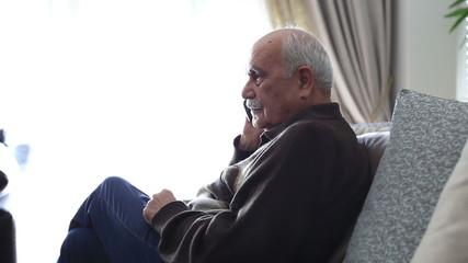 Senior Man using smartphone and talking at home