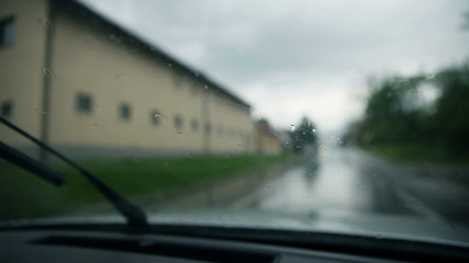Close up on windshield while rain drops falling and wipers cleaning