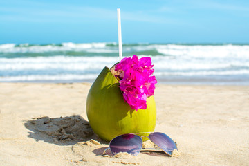 Coconut and sunglasses on the beach