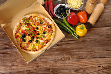 Freshly baked Pizza in delivery box with ingredients.