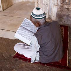 Man with Kuran praying and reading