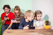 Children with parents sit with gadgets, playing game in phones