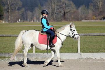 junges Mädchen reitet auf Pferd