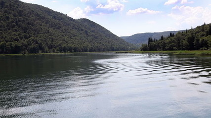 Panoramic shot of river Krka`s shore made from the moving boat
