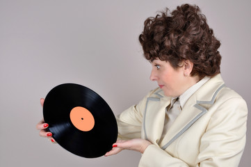 Pleasantly surprised woman holding and looking at a vinyl record