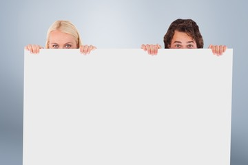 Composite image of happy couple hiding behind a whiteboard