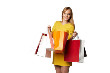 Shopping young woman in the yellow with bags isolated on white b