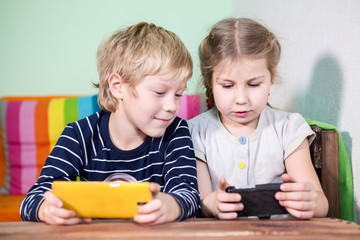 Brother watching screen of cellphone in sister hands