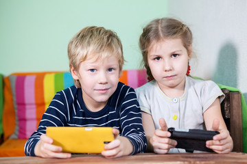 Two pretty kids with smartphones in hands looking at camera