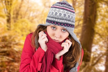 Composite image of cold redhead wearing coat and hat